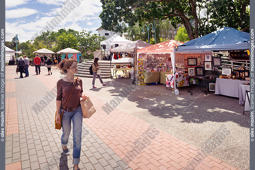 Young woman walking past farmer's market vendors at Pioneer Waterfront Plaza in downtown Nanaimo, Vancouver Island, British Columbia, Canada 2017
