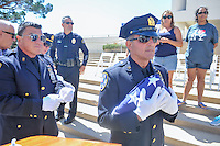 New York Port Authority detective Frank Accardi holds an American flag that was presented to the city of Huntington Beach. The flag was flown over the new World Trade Center and was flown during today's ceremonies.<br /> <br /> ///ADDITIONAL INFORMATION: hb.0915.memorial &ndash; 9/11/16 &ndash; MICHAEL KITADA, ORANGE COUNTY REGISTER - _DSC8537.jpg - <br /> Summary: The Huntington Beach Police Officers' Foundation's 9-11 Memorial Committee unveils a $200,000 monument including steel from the toppled World Trade Center, at City Hall. The event will include music, a flyover, New York police and others with connections to the 9-11 rescue and victims of the tragedy.