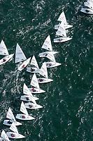"""Kieler Woche:EUROPA, DEUTSCHLAND, SCHLESWIG- HOLSTEIN 22.06.2005:Kieler Woche, Segler der Laser Klasse im Gedraenge beim Regattastart.<br /><br />Der Laser ist eine 4,23 m lange, 1,37 m breite und 57 kg (Rumpf) schwere Einmann-Jolle mit einem Segel.<br /><br />Der Laser wurde 1970 vom Amerikaner Bruce Kirby als Einhand-Jolle entworfen. Primaere Zielsetzung war damals ein Boot für die Freizeit zu entwerfen, deshalb auch der ursprüngliche Name """"Freetime"""".<br />Seine einfache Bauweise und niedrige Anschaffungskosten führten zu einer raschen Ausbreitung. Ende des Jahres 2004 gab es ca. 180.000 Boote auf der Welt!<br />Der Laser ist eine One-Design Bootsklasse und wird von der Firma Performance Sailcraft Ltd. in England gefertigt. Weiterhin gibt es Lizenznehmer in Australien und in Chile.<br />Das Niveau in der Laser-Klasse gilt als eines der höchsten der olympischen Bootsklassen<br /><br />Luftaufnahme, Luftbild,  Luftansicht"""