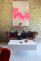 Hugo Rittson-Thomas photographed beneath an abstract painting hanging on the stone wall of the Art Barn; in front a coffee table with a transparent acrylic base seems to float in space