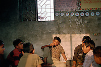 Boys who work at the Mohammadpur rice market sit during a class organized for them by Phulki. If their employers allow them, they can attend this informal school every day.
