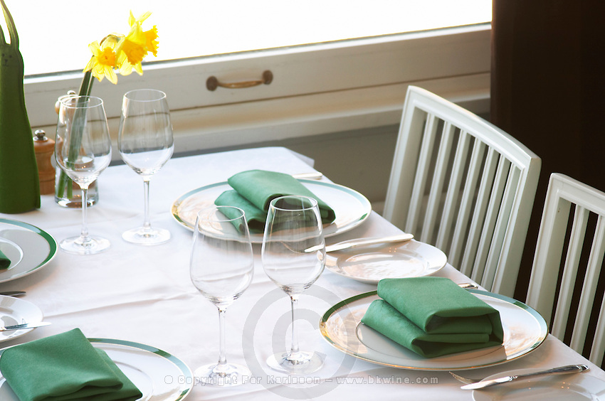 A restaurant table with a white linen table cloth set for four persons, with plates, silver cutlery and green napkins and a yellow Easter daffodil lily flower on the table. Ulriksdal Ulriksdals Wärdshus Värdshus Wardshus Vardshus Restaurant, Stockholm, Sweden, Sverige, Europe