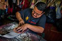 A Salvadoran shoemaker cuts a shoe upper from a fiber sheet on the workbench in a shoe making workshop in San Salvador, El Salvador, 16 November 2016.