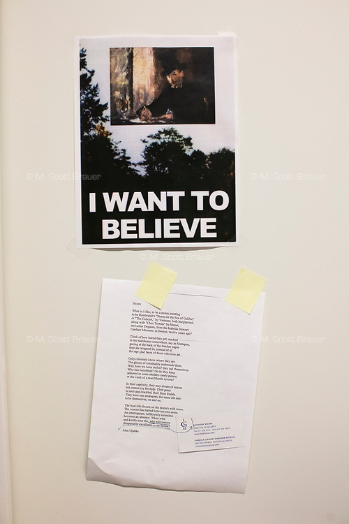 """A poster and a poem hang on a wall in the office of Anthony Amore, the Directory of Security and Chief Investigator at the Isabella Stewart Gardner Museum in Boston, Mass., USA, seen here on Tues., Dec. 5, 2017. The poster on top, reminiscent of Fox Mulder's """"I Want to Believe"""" poster in the X-Files, features a reproduction of Manet's """"Chez Tortoni"""" in place of the UFO. The poem is a piece written by John Updike about the Gardner Museum theft.  Part of Amore's ongoing work is the investigation into the 1990 theft of 13 pieces from the museum: 10 paintings, 2 objects, and 1 etching. Among the paintings stolen were works by Rembrandt, Vermeer, Degas, and Manet. """"Chez Tortoni"""" is one of the paintings that was stolen in the heist."""