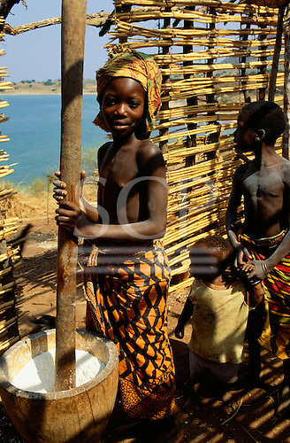 Yumba, Tanzania. Girl pounding cassava in a wooden bowl in a part finished house with her brother and sister.