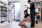 Tokyo, April 26 2013 - Young wrestler Ginseizan Takahiro, 20, drinking after training, while an older wrestler is having his hair done at Otakebeya sumo stable.