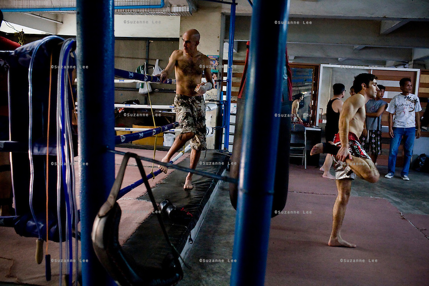 "Shuki (left) looks on as Gili (3rd from right) warms up in Rompo Muay Thai Gym, Khlong Toei, Bangkok city, Thailand on 14th December 2009..Shuki Rosenzweig, aged 40, is a professional Muay Thai Boxing fighter (champion) and trainer who has lived for 9 years in Thailand. He is famous in Israel as the authority of this sport. Started at the age of 12 in boxing in Israel, Jerusalem. Used to work in the fish market. His father is a 'legend' in Jerusalem fish market. Shuki stopped working with his dad about 13 years ago. He has opened some muay thai gyms in Thailand in the past. He currently has about 5 Israeli fighters under his training in Bangkok, besides fighters of other nationalities. Shuki found religion in Bangkok with Chabad about 4 years ago. He never misses Shabbat and loves to sing the songs of prayer, priding himself with a good voice. ""Chabad integrates all Jews. it keeps us together. When at Chabad, we are at home, united with people of the same culture, language and beliefs""..Gil Saat (known affectionately as Gili), aged 29, from Ramat Gan, Israel, has been a boxer for 9 years. He is on his second trip to Thailand for muay thai. On the first trip, he stayed for 6 months, fighting in about 10 competitions in Thailand and once in Cambodia. Gili has graduated in many sport related courses from institutes in Thailand and Israel, including a diploma in Thai massage. He first met Shuki in Israel many years ago at a competition when Shuki was the trainer for Gili's opponent in the ring. A few years after that, Gili attended a seminar given by Shuki about muay thai and then decided to come to Thailand to train under him. Gili comes from a more religious family in comparison to Shuki. Gili's grand father is a rabbi in Israel. Gili introduced Shuki to Chabad (both Khao San and Sukhumvit) about 4-5 years ago and they have since spent every shabbat at Chabad. On 4th Dec 2009, they both turned up for shabbat immediately after a competition, still bleeding and Shuki wi"