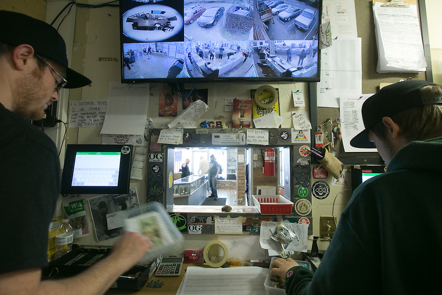 "Cashiers ring up sales as ""bud tenders' place orders through a window at Main Street Marijuana in downtown Vancouver February 14, 2017. (Photo by Natalie Behring for the Columbian)"
