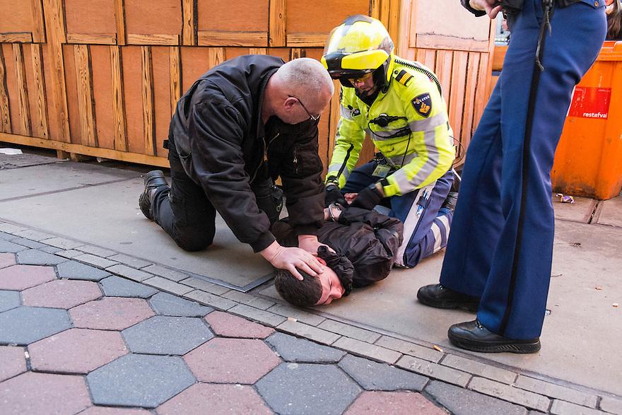 Nederland, Amsterdam, 11 jan 2014<br /> Op het Damrak wordt een verdachte gearresteerd door de politie.  Tijdens het omdoen van handboeien wordt hij tamelijk hardhandig met zijn hoofd op het trottoir gedrukt. <br /> Foto: Michiel Wijnbergh