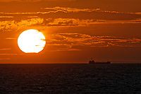 A ship sails while the sun sets in the English Channel as seen from near the port of Calais in France towards Dover. Wednesday 04 September 2019
