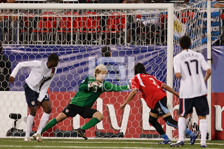 USA goalkeeper (18) Brian Perk makes a save off a header by Uruguay defender (3) Martin Caceres in overtime. The United States (USA) defeated Uruguay (URU) 2-1 in overtime during a FIFA U-20 World Cup round of 16 match at the National Soccer Stadium at Exhibition Place, Toronto, Ontario, Canada, on July 11, 2007.