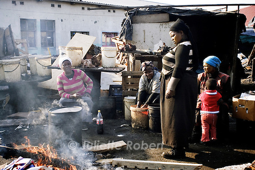 Women cook sheep heads to be sold, in Langa (township near Cape Town). April 2009