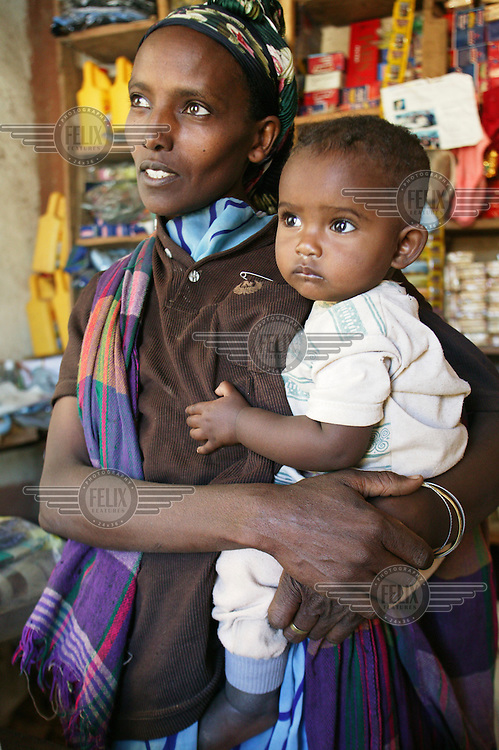 Sadia in her village shop with her son. The shop is run with the help of a community cooperative, which is made up of 30 women.
