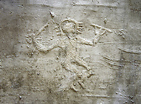 Cast of a prehistoric Petroglyph, rock carving, of a warrior dancing with a sword and shiled carved by the Camunni people in the iron age between 1000-1600 BC , Foppi di Nadro rock 24, Seradina-Bedolina Archaeological Park Museum, Valle Comenica, Lombardy, Italy