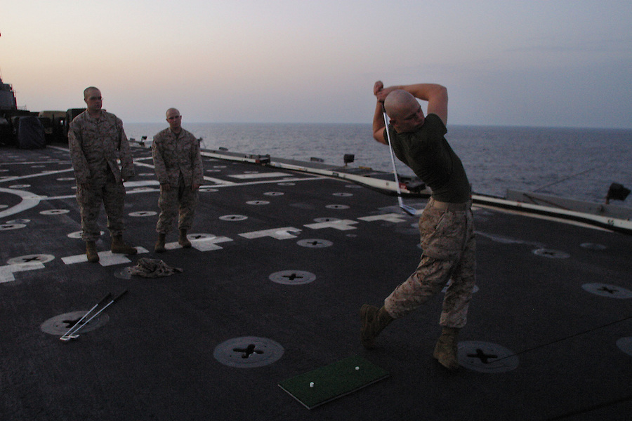 "A Marine works on his swing sending balls arcing off the rear of the USS Denver's flight deck. The balls and clubs are provided by the ship's ""Morale, Wellfare, and Recreation"" office which does what it can to ease the repetition and tedium of the transit."