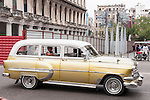 Havana, Cuba; a classic gold colored 1954 Chevy Bel Air station wagon drives down the street in Havana