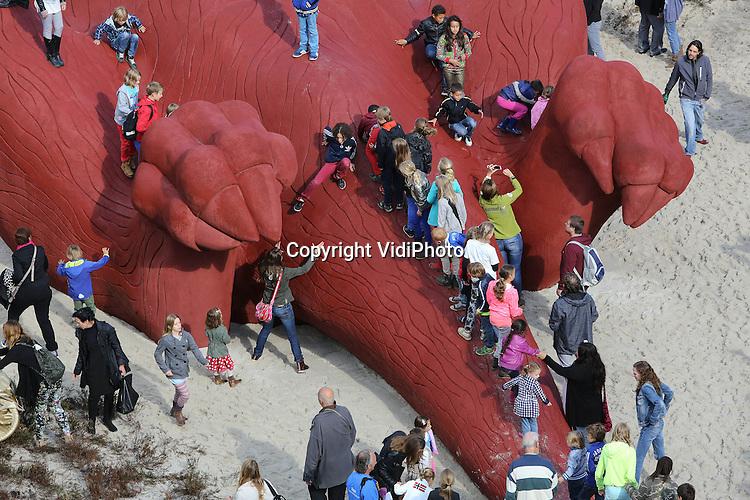 Foto: VidiPhoto<br /> <br /> ARNHEM - Het Feestaardvarken, een geschenk van de honderdjarige Burgers' Zoo aan de stad Arnhem, is donderdag in de binnenstad officieel in gebruik genomen. Een hondertal kinderen mocht de strik om het varken lostrekken. Het Feestaardvarken ligt op z'n rug in de binnenstad in een bed van heide. Het is het grootste kunstwerk van Nederland, waar bovendien op gelopen en gespeeld mag worden. Het beest weegt bijna 150.000 kilo, is 30 meter lang, 9 meter hoog, 13 meter breed en is van metaal en beton. Burgers' Zoo is het enige dierenpark in Nederland met aardvarkens.