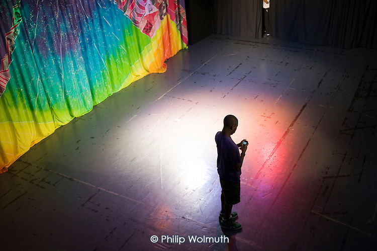 A choreographer uses a mobile phone during a pause in rehearsals at Paddington Arts youth performaing arts project.