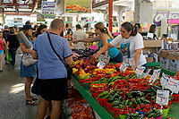 People shopping at a vegetable vendor's stall in Jean Talon public market or Marche Jean Talon, Montreal, Quebec, Canada