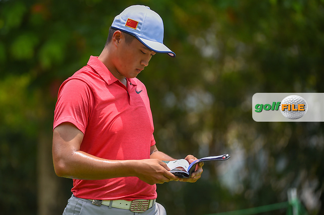 Zheng Kai BAI (CHN) looks over his yardage book as he heads down 5 during Rd 2 of the Asia-Pacific Amateur Championship, Sentosa Golf Club, Singapore. 10/5/2018.<br /> Picture: Golffile | Ken Murray<br /> <br /> <br /> All photo usage must carry mandatory copyright credit (© Golffile | Ken Murray)