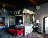 A traditional four-poster bed is complimented by a daybed upholstered in red corduroy