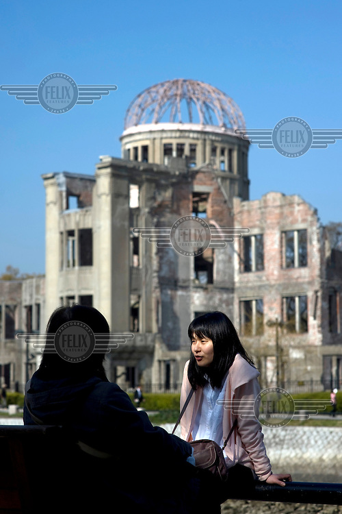 Two women talk in front of the Hiroshima Peace Memorial (Genbaku Dome). It was the only building left standing at the hypocentre of the bomb blast following the detonation of the 'Little Boy' atomic bomb, dropped on 6 August 1945. /Felix Features