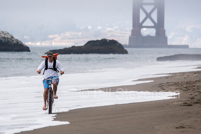 A photo of a man riding a cruiser bike through the surf on a beach near the Golden Gate Bridge in San Francisco, CA.