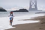 A photo of a man riding a cruiser bike through the surf on a beach near the Golden Gate Bridge in San Francisco, CA.