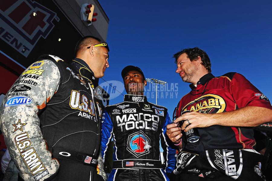 Oct. 30, 2011; Las Vegas, NV, USA: NHRA top fuel dragster drivers Tony Schumacher (left), Antron Brown (center) and Del Worsham talk before the Big O Tires Nationals at The Strip at Las Vegas Motor Speedway. Mandatory Credit: Mark J. Rebilas-