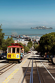 USA, California, San Francisco, a trolly drives up Hyde street with the San Francisco Bay and Alcatraz in the distance