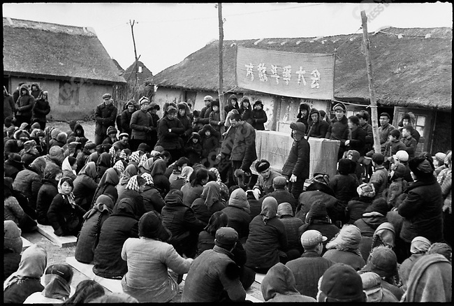 "Under a banner that reads ""Struggle against the enemies rally,"" Zhang Diange is denounced as a rich peasant by members of the Nansheng production brigade and made to bow his head for hours. Ashihe commune, Acheng county, Heilongjiang Province, 25 March 1965"