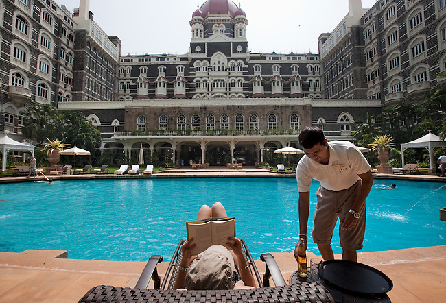 MUMBAI, INDIA - SEPTEMBER 27, 2010: A waiter serves a drink by the pool at The Taj Mahal Palace and Tower Hotel in Mumbai. The hotel  has re-opened after the terror attacks of 2008 destroyed much of the heritage wing. The wing has been renovated and the hotel is once again the shining jewel of Mumbai. pic Graham Crouch