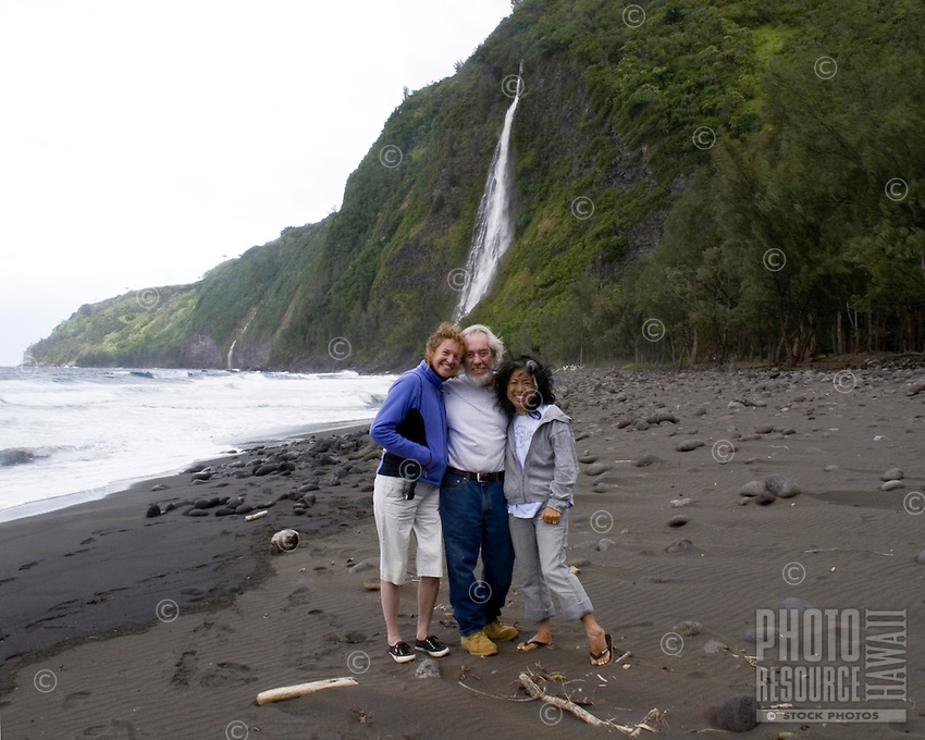 Three friends on a black sand beach with waterfall in Waipio
