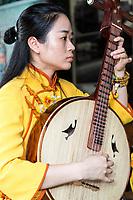 Cangpo, Zhejiang, China.  Young Woman Playing a Ruan (Chinese Banjo) in a Chinese Opera Orchestra.