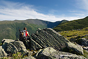 A hiker enjoys the view of Mount Washington from Six Husbands Trail during the summer months in the White Mountains, New Hampshire.