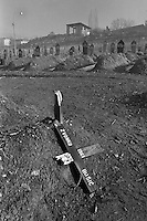 A broken cross marks a grave in an improvised cemetery in a soccerfield in the besieged Bosnian captial Sarajevo on January 10, 1993. The graves in the background have muslim headboards.