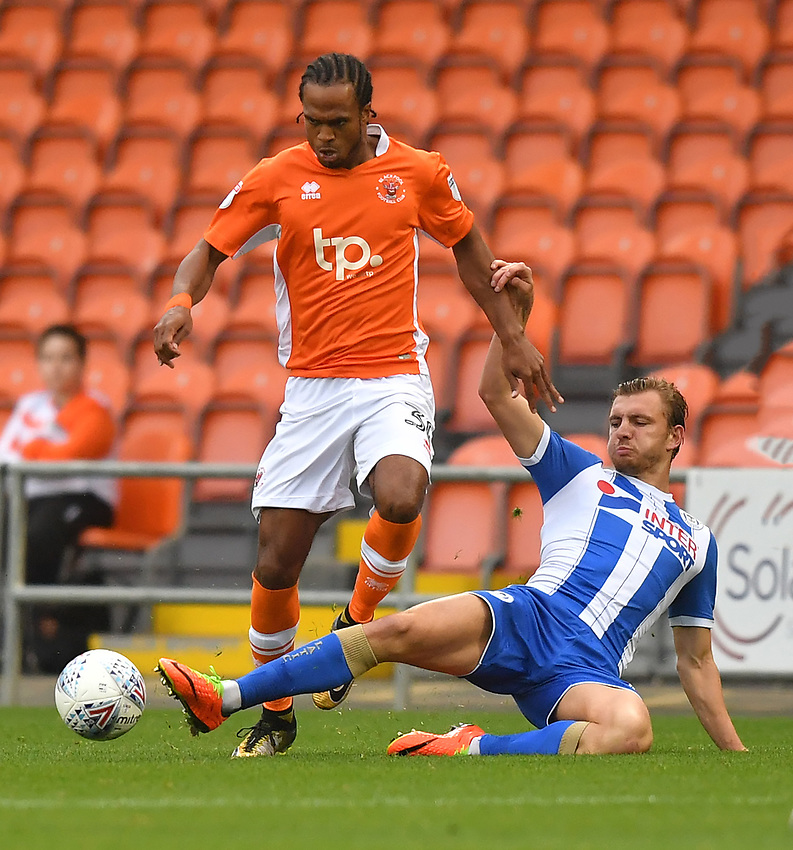 Blackpool's Nathan Delfouneso is tackled by Wigan Athletic's Gavin Massey<br /> <br /> Photographer Dave Howarth/CameraSport<br /> <br /> The EFL Checkatrade Trophy - Blackpool v Wigan Athletic - Tuesday 29th August 2017 - Bloomfield Road - Blackpool<br />  <br /> World Copyright &copy; 2018 CameraSport. All rights reserved. 43 Linden Ave. Countesthorpe. Leicester. England. LE8 5PG - Tel: +44 (0) 116 277 4147 - admin@camerasport.com - www.camerasport.com