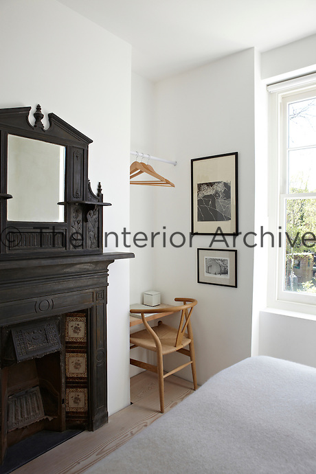 A white bedroom with an original Victorian fireplace with an overmantel. A simple wood chair is placed at a desk-shelf set in the recess beside the chimney breast.