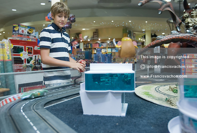 Quebec city, August 1, 2008 - Drew Brewster, 12, plays with the electric race track on display  at the Benjo toy store on St-Joseph street in Quebec city. Benjo is a 28,000-square-foot game and toy store filled with dolls, teddy bears, crafts, candy, model trains and cars, and more.