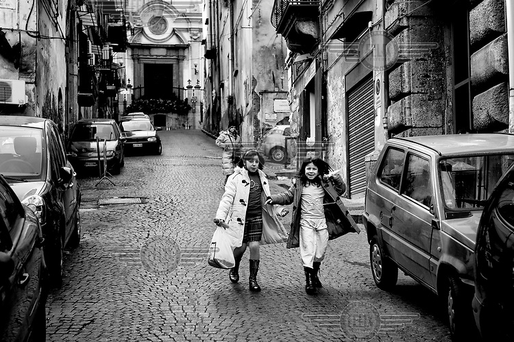 Two young girls walk along one of the cobbled, narrow lanes of the Quartieri Spagnoli (Spanish Quarters).