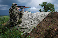 A Russia-backed rebel looks through sniper rifle toward ukrainian positions at the frontline near Dokuchaevsk, eastern Ukraine, Friday, June 5, 2015. As fears persist that eastern Ukraine is about to fall back into full-scale war, a leader of the international monitoring group is urgently calling for resumed negotiations.