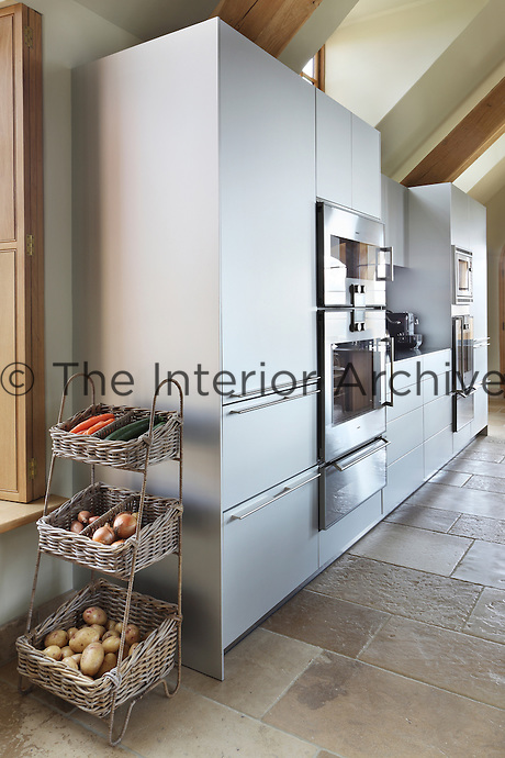A stand of natural baskets for vegetables contrasts with the sleek contemporary design of the kitchen