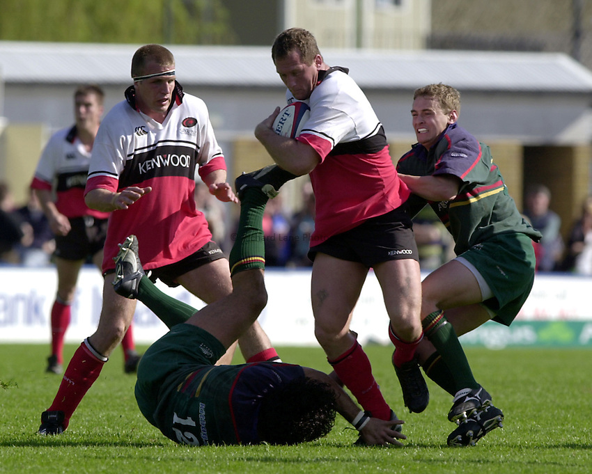 Photo. Richard Lane. .London Irish v Saracens 29/4/2000.Richard Hill breaks through the tackles of Robert Todd and James Brown.