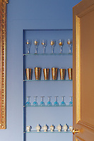 A gold-painted door opens in to the Wedgwood blue and gold dining room where glass shelves display a collection of wine glasses