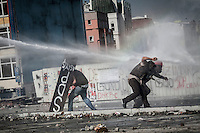 In this Tusday, Jun. 11, 2013 photo, protesters run for cover as the anti-riot police charge against them by water canyons during clashes at the streets of Taksim Square in Istanbul,Turkey. (Photo/Narciso Contreras).
