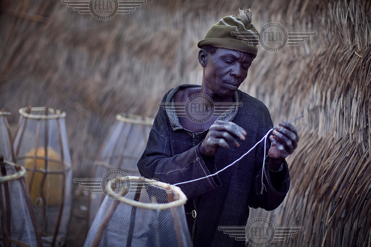 A man fixes a fishing net beside Lake Chad. With declining waters and increasing population, fish stocks have declined on Lake Chad. The lake is drying up, due largely to desertification as the Sahara advances southward. This advance is caused in part by global warming which has reduced rainfall in the region, weakening plants whose roots once held topsoil in place. The lake is also drying up because water is pumped out from the lake by government sponsored irrigation schemes.