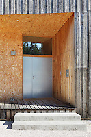 The entrance to the property is constructed of compressed wood off cuts and the walls are clad in chestnut wood
