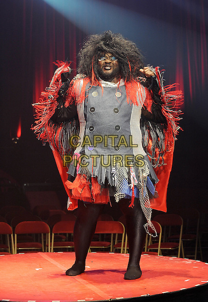 Le Gateau Chocolat.Performing at a press call to promote 'La Soiree', a new unique theatre show with a heady cocktail of cabaret, new burlesque and circus sideshows, Roundhouse, London, England..24th November 2011.stage performance performing full length black tights jacket grey gray red tassels fringed wig hands arms.CAP/BEL.©Tom Belcher/Capital Pictures.