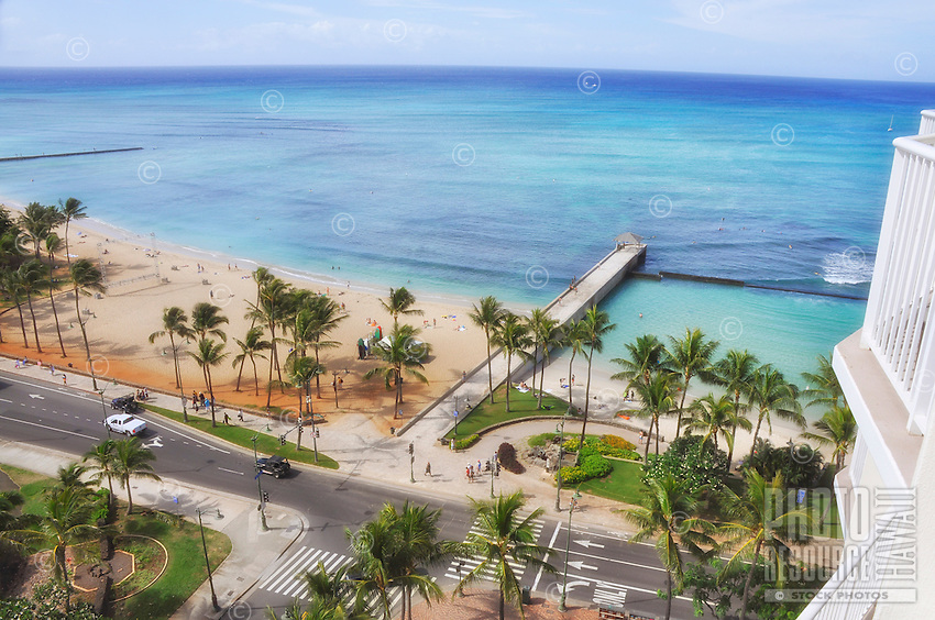 A hotel visitor's balcony view of Queen's Beach to the left and Kuhi'o Beach Park to the right, with the Kapahulu Avenue storm drain extension in between, Waikiki, O'ahu.