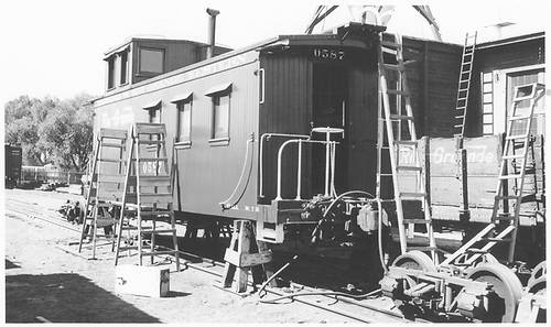 3/4 view of caboose #0587 in car shop at Alamosa, 7/56.<br /> D&amp;RGW  Alamosa, CO  Taken by Maxwell, John W. - 7/1956